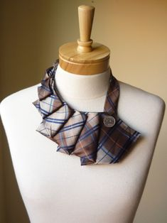 Here is an unusual bib necklace made out of a recycled vintage tie. This particular one is a brown tartan, with a hint of navy blue, light blue,