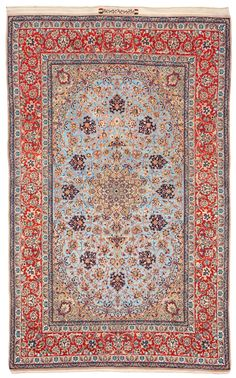 OLD ESFAHAN. 243 x 152,5 cm. A light blue melange ground with a polychrome medallion, corner ornaments, cloud bands, palmette and flower festoons. A red main border with a palmette and flower vine. The lower end has an inscription.