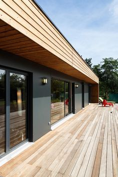 terrasse en bois dans le prolongement de la maison design avec revêtement de façade en bois clair