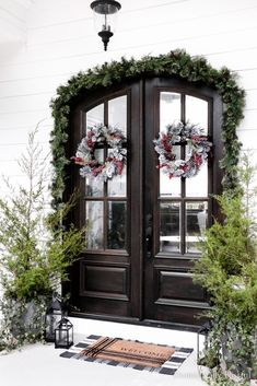 Simple Front Porch Christmas Decor using fresh-cut evergreen trees from our woods and layered Christmas garland. | Fresh cut evergreen trees on a front porch. | Red front porch Christmas decor. | Frosted wreaths for Christmas. | Easy Christmas decor for your front porch. | White house Christmas decor. | White shiplap house with double doors stained dark brown. Simple Christmas, Christmas Home, Christmas Tree Ornaments, Christmas Crafts, Christmas Ideas, Homemade Christmas Decorations, Holiday Decorations, Holiday Ideas, Winter Home Decor