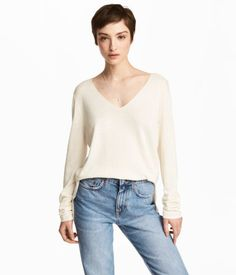 Natural white. Straight-cut, V-neck sweater in soft, fine-knit viscose-blend fabric with long sleeves and slits at sides. Slightly longer at back.