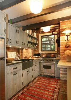 The kitchen has a rustic retro vibe with an ethnic twist. We like how the charcoal painted beams and washed cabinets introduce cool tones to the brick and red runner.