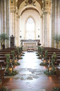 European-inspired lanterns accented with organic greenery. #wedding #aisle #markers