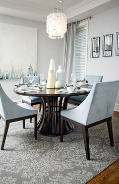 I love this cool blue-grey dining room. The chairs are from West Elm and that painting is very intriguing.
