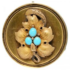 A VICTORIAN GOLD BROOCH-PENDANT, APPLIED WITH A GOLD VINE LEAF AND SET WITH THREE SPLIT TURQUOISES, GLAZED BACK, 9.6G  Sold @ Mellors & Kirk