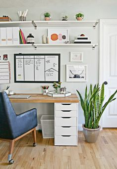 I really like how there are some functional elements to this space...the white board, the white magazine holders, plus some playful elements like the plants and art.