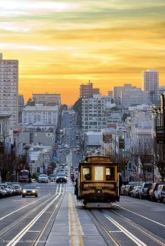 San Francisco, CA, USA ....A cable car rolls down western California street (past Nob Hill and Grace Cathedral) while wispy clouds form a golden sunset on a chilly December day.