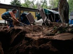 Local resident Sanya Tuttle recovers parts of her home from debris left by the floods in Lyons