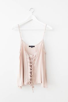 Minimal tank with a lace-up front and thin adjustable straps. Loose flowy fit. Lightweight semi-sheer non-stretch material. Model is wearing size small. - 100% Rayon - Imported