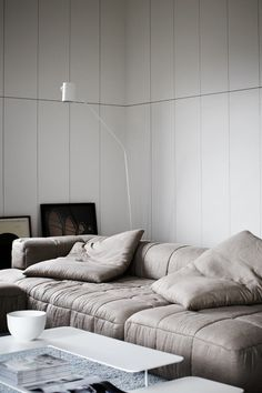 A seating concept that uses large pillows and small rectangular ones to emulate a couch.