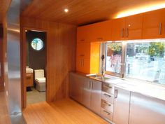 Shipping Container Homes - kitchen & bath - orange cabinets (metal strip in foreground lines the walkway opening between the two containers)
