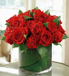 red roses and  red carnations with complimentary leaves