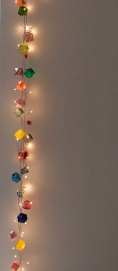 Instead of putting lights in the boxes, you could just intertwine them with an origami box garland. | #ChristmasDesigners | www.christmasdesigners.com