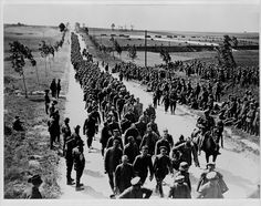WW1: A long column of German POWs is marched behind British lines en route to internment. Australian troops, wearing the characteristic Australian hat, are watching. Taken POW had its advantages for both sides: the captured were removed permanently from the trenches thus improving their chances of survival dramatically.