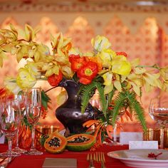 tropical centerpiece with papaya and orchids, by Ariella Chezar, photo by Meg Smith