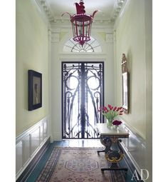 A Charles Edwards lantern adds a splash of color to the entrance hall of a townhouse   archdigest.com