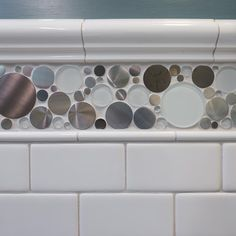 Jazz up classic white subway tile with an accent tile, like the steel-and-glass bubble choice in this kid's bathroom.