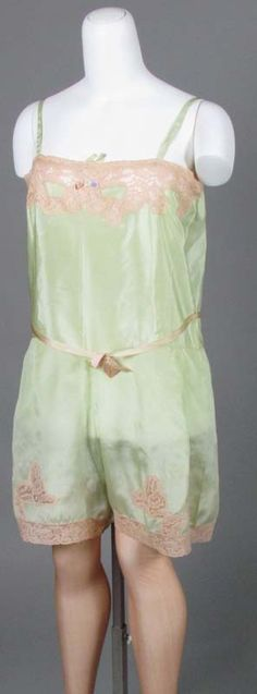 """Green silk """"envelope chemise"""" or """"step-in"""" slip, 1920s. Most of the Victorian undergarments were abandoned, and silks and colors entered underwear. With a """"good"""" figure, by the mid-20s, this might be all you needed under your dress. Most women's figures required some support and shaping to eliminate and smooth bust, hips, waist, and behind, using a brassiere and the new hip-level corset."""