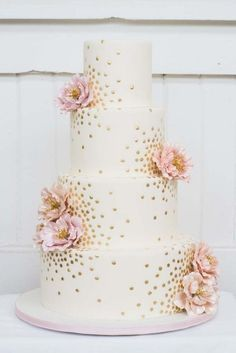 4 tier white wedding cake with gold polka dot with pink flowers
