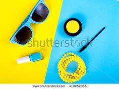 Summer accessories and cosmetics for relaxation on a yellow background - sunglasses, lipstick, powder, colored beads, nail polish. View from above. Flat lay.
