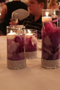 DIY purple centerpiece- fill vases w/ silk rose petals, fill with water & float a candle on top! Silver 'diamond' ribbon hot glued around the bottom. That's it!