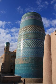 """Kalta Minor Minaret - Khiva Uzbekistan """"Just south of the Kuhna Ark stands the fat, turquoise-tiled Kalta Minor Minaret. This unfinished minaret was begun in 1851 by Mohammed Amin Khan, who according. Persian Architecture, Mosque Architecture, Art And Architecture, Laos, Philippines, Timor Oriental, Moorish, Central Asia, Islamic Art"""
