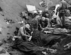 80-G-435702: Iwo Jima Operation, 1945. U.S. Navy doctors and corpsmen administer to wounded Marines at an Iwo Jima first aid station, 20 February 1945. Navy Chaplain Lieutenant (Junior Grade) John H. Galbreath (right center) is kneeling beside a man who has severe flash burns, received in an artillery battery fifty yards or so away. Photographed by Warrant Officer Obie Newcomb, Jr., USMCR. Official U.S. Marine Corps Photograph, now in the National Archives' U.S. Navy photographic collection.