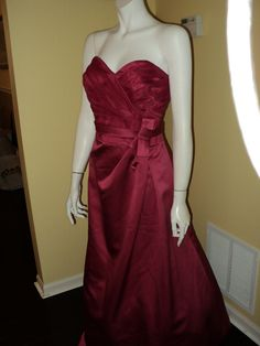 This red, satin gown has gorgeous details: including a sweetheart neckline and a bow.