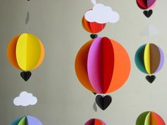 The bright shades of this hand-made hot air balloon mobile are perfect to add a touch of happiness and a ton of colour to your babys nursery. In