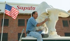 """Jamie Hitchcock does touch-up work on the cow [and milkmaid] that is part of the sculpture in front of Saputo Dairy Foods, 605 No. J St. The statue is one of 25 that Adohr Farms commissioned in 1927 and placed at its creamery sites, including the one in Tulare. - """"Largest Guernsey herd in the world"""" - Oct. 2, 2014, Tulare Voice"""
