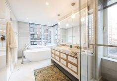 For a futuristic glow from the mirror, this bright city bathroom with pendant lighting skips recessed lights in the vanity area, and instead includes two eye–catching pendants that incorporate indirect lighting over the sink