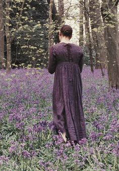 Walking in the woods, with a field of flower covering her feet.