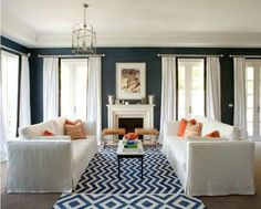 High white drapes on a royal blue background makes the room look very tall and not so dark.