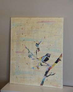Mod Podge cut-up magazines onto a canvas, put a stencil down and paint around it. Then sand a little, and add more streaks and splatters of paint.
