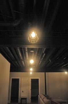 Finished basement space with painted black ceiling and warehouse cage lights. The black ceiling really makes the basement feel taller! Types Of Ceilings, Cage Light, Ceiling Design, Diy Basement, Ceiling, Lights, Basement Ceiling Ideas Cheap, Basement Ceiling Painted, Industrial Home Design