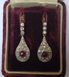 1920's Art Deco Platinum And 18kt gold Backs Cabochon Ruby And Diamond Drop Pendant Earrings For Pierced Ears. Diamond Weight Approximately !.50 cts And Rubies Weighing Approximately 50 ct each Total Weight of Rubies 1 carat with exempflying handmade open workmanship American made.