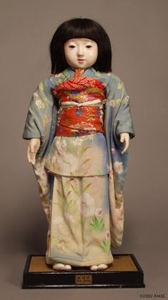 Miss Nagasaki is 81 cm tall, and was made by Mr. Khoryusai of Yoshitoku Dolls, Tokyo. All but a few of the ambassador dolls were made by this firm of master doll makers. Miss Nagasaki's head, limbs, and upper and lower body are made primarily of wood, with joints between the limbs provided by sections of cloth. The wood is covered with many layers of powdered shell called gofun. The final layer is polished to produce a very smooth surface, which is then painted. Her eyes are glass and she…