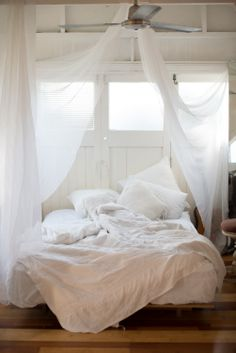 A mosquito net in a white bedroom is like summer romance.