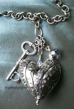 A STERLING SILVER HEART WITH A KEY.