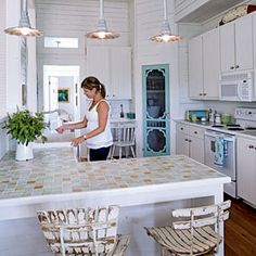 Charming Touch    Small details can make a big impact! The pretty detailing, soft blue color, and conch shell knob of the screened pantry door add casual, beach cottage style to the kitchen.