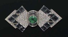 EMERALD, ROCK CRYSTAL AND DIAMOND DOUBLE CLIP BROOCH, SUZANNE BELPERRON, circa 1935. Platinum and white gold. Of triangular design decorated with engraved rock crystals and set throughout with 112 old mine-cut and octagonal diamonds totalling ca. 4.00 ct, connected with 1 engraved rock crystal half loop enhanced with 1 emerald cabochon of ca. 3.30 ct. ArtDeco