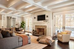 Garrison Hullinger Interior Design - living rooms - living room beams, living room ceiling beams, paneled living room ceiling, living room paneled ceiling, board and batten, living room board and batten, board and batten living room, gray sectional, gray sectional sofa, faux snakeskin ottoman, faux python ottoman, ottoman coffee table, python ottoman, snakeskin ottoman, floor pillows, suede floor pillows, traditional fireplace, fireplace with corbels, fireplace corbels, french doors, living room french doors, millwork, fireplace millwork, tv niche, flatscreen niche, flatscreen tv niche, fireplace niche, fireplace tv niche, fireplace flatscreen niche, fireplace flatscreen tv niche, cowhide floor pillows, rust orange throw, stone fireplace surround,