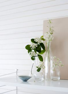 A group of different shaped vases with flowers from the garden in a delightful home in Finland / Riika Kantinkoski