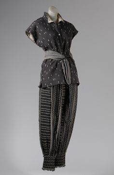 Issey Miyake, 1983. Dark gray cotton and wool. Emblematic of Miyake's cross-cultural confluence, this ensemble exhibits the raw color and craftsmanship of African mud cloth style resist patterns, yet champions the Turkish trousers, sash belt, and sleeveless bodice of Eastern European regional costume.