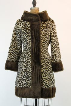 Classic leopard print coat with a twist! Done in a faux fur leopard with chocolate brown. Wide funnel standup collar. Bracelet length sleeves with
