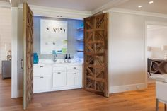 Double carved wood doors opens to a hidden bar filled with white cabinets and calcutta marble countertops fitted with a bar sink and gooseneck faucet placed below art lining a blue textured wall flanked by  lighted stacked floating shelves lined with wine glasses.