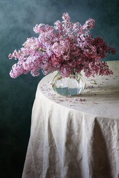 http://nikolay-panov.pixels.com/products/purple-lilacs-nikolay-panov-art-print.html floral still life photography with simple composition of bouquet of purple lilacs in glass vase on crumpled drapes with cold blue background on daylight in spring