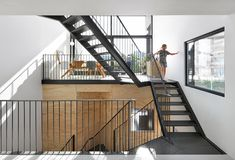 Inside this wooden, prefabricated house in Amsterdam by Marc Koehler Architects, an angular black staircase crisscrosses between split levels.