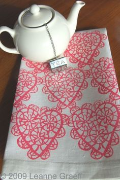 Plain white teapot and a fun heart table cloth (I gotta find a way to make this towel; too cute!)