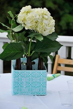 My centerpieces...cute contact paper on 6 pack holder and hydrangeas and greenery in beer bottles :)